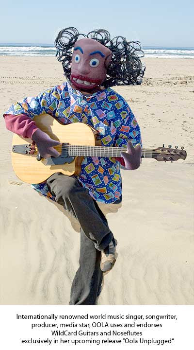 Oola plays a Mr. Rioso guitar on the beach at Morro Bay