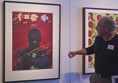 Curator Joe McDonald discussing a Raymond Saunders print